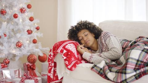 Woman sleeping in front of decorated tree